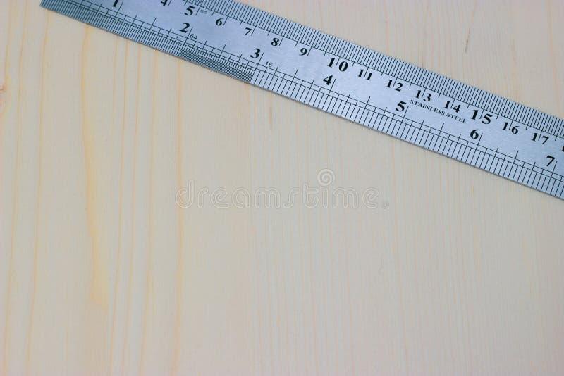 Régua da carpintaria do metal em um fundo de madeira claro foto de stock