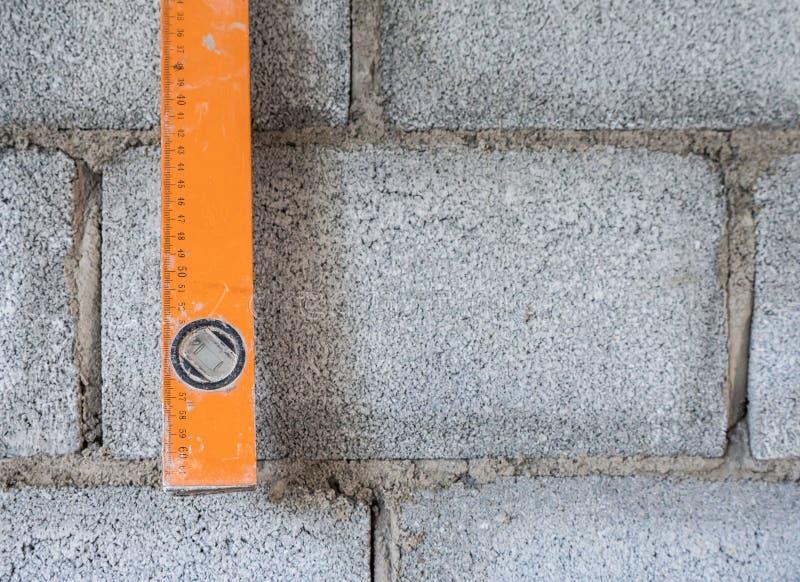 A régua nivelada suja está pendurando perto da parede de tijolo foto de stock