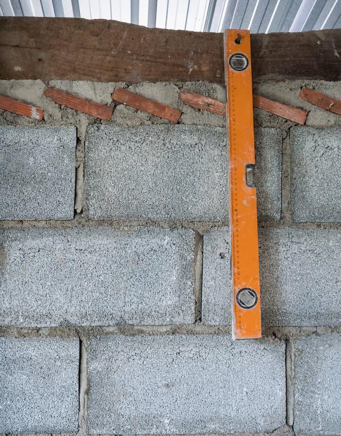 A régua nivelada velha está pendurando na parede de tijolo fotografia de stock royalty free