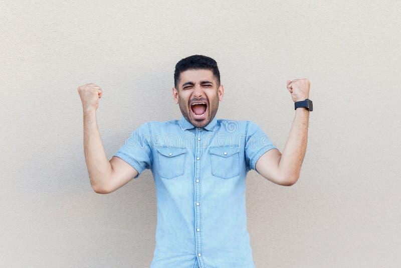 R?jouissance d'homme de gagnant Portrait de jeune homme d'affaires barbu beau ?tonn? dans la position bleue de chemise, criant et photo stock