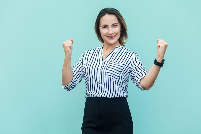 Réjouissance de femme d'affaires pour son succès sur bleu-clair photographie stock libre de droits