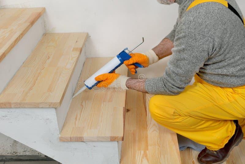 Rénovation à la maison, calfeutrant les escaliers en bois avec du silicone image stock
