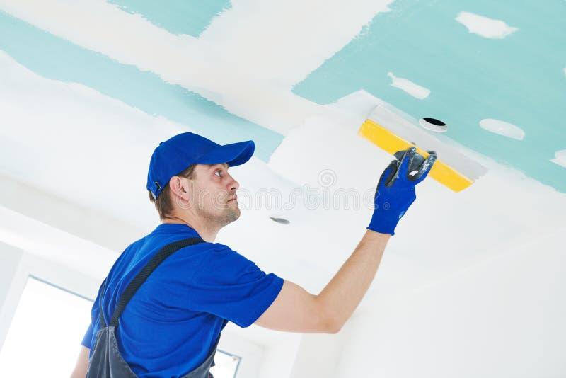 rénovation Plâtrier spackling un plafond de plaque de plâtre de gypse avec le mastic photographie stock libre de droits