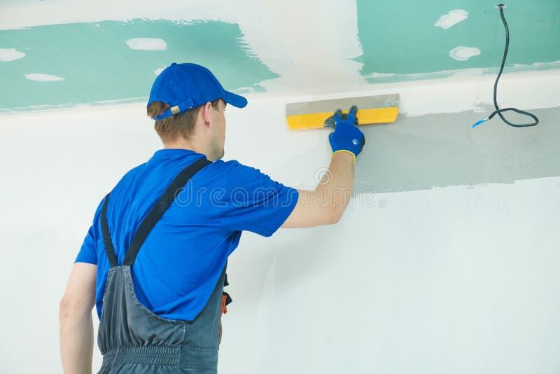 rénovation Travailleur de plâtrier spackling un mur avec le mastic photo libre de droits