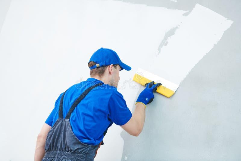 rénovation Travailleur de plâtrier spackling un mur avec le mastic photos stock