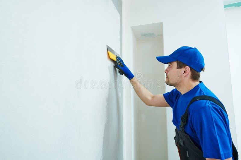 rénovation Travailleur de plâtrier spackling un mur avec le mastic photos libres de droits