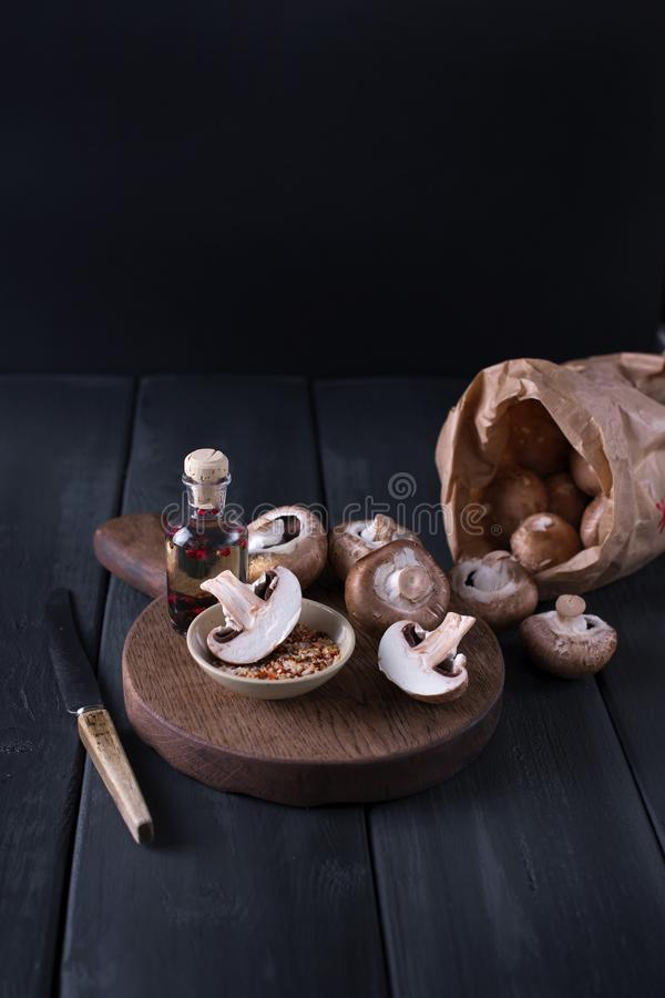 Répand les champignons de paris dans un sac de papier, sur un conseil en bois et un couteau sur le fond Copiez l'espace image stock