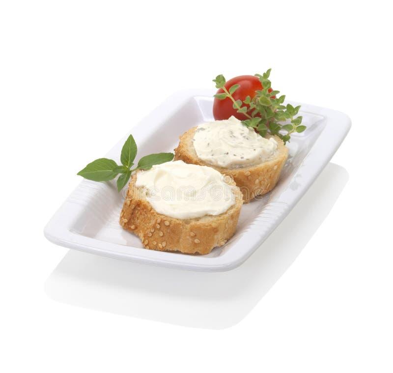 Répandez le fromage sur le pain photo stock