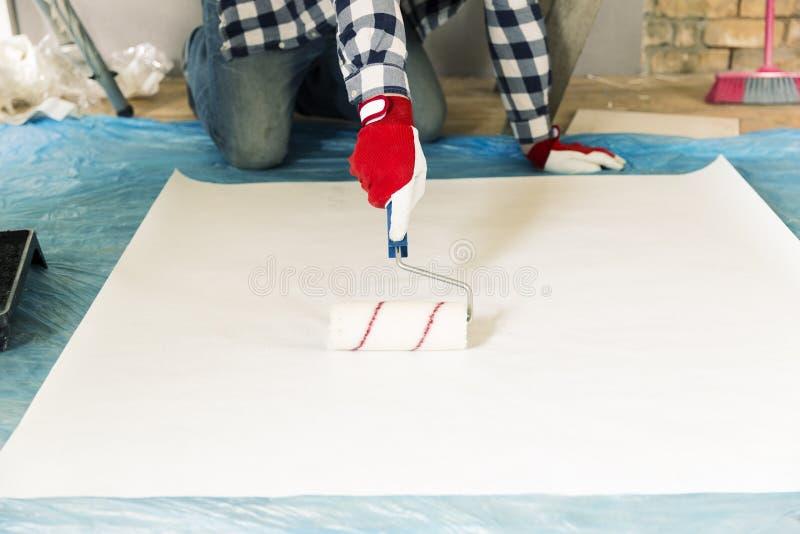 Réparation, bâtiment et concept à la maison de rénovation - fermez-vous des mains masculines enduisant le papier peint de la coll images stock