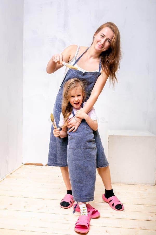 Réparation dans l'appartement La mère et la fille heureuses de famille dans les tabliers ont disposé à peindre le mur avec la pei photo libre de droits