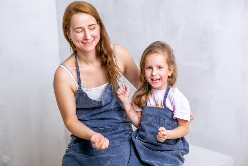 Réparation dans l'appartement La mère et la fille heureuses de famille dans les tabliers peignent le mur avec la peinture blanche images libres de droits