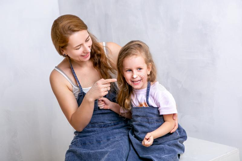 Réparation dans l'appartement La mère et la fille heureuses de famille dans les tabliers peignent le mur avec la peinture blanche photo stock