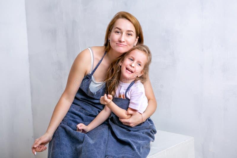Réparation dans l'appartement La mère et la fille heureuses de famille dans les tabliers peignent le mur avec la peinture blanche photographie stock libre de droits