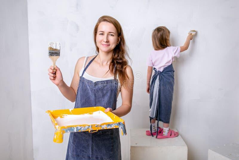 Réparation dans l'appartement La mère heureuse de famille et la petite fille dans les tabliers bleus peint le mur avec la peintur images stock