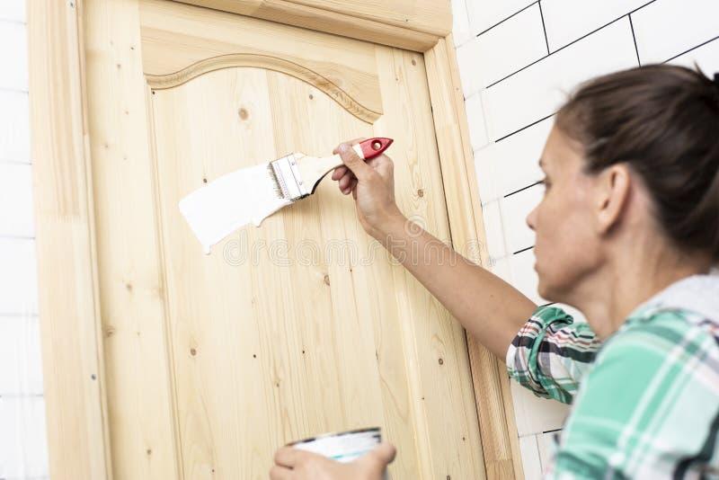 Réparation de Chambre La femme peint une porte en bois dans la salle de bains dans la couleur blanche avec une brosse Photo horiz images stock