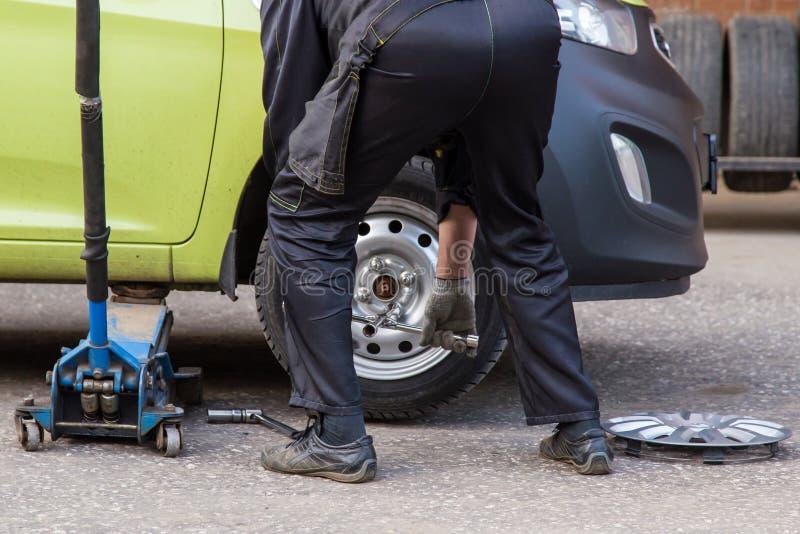 Réparation de la roue, pneu d'une voiture cassée de mécanicien image stock