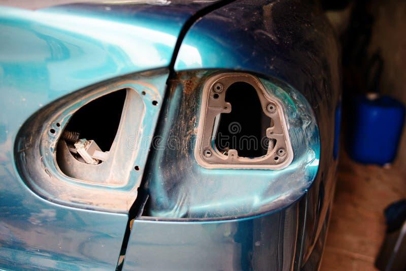 Réparation de plan rapproché d'une voiture bleue cassée dans le garage à la main de machanic photo libre de droits