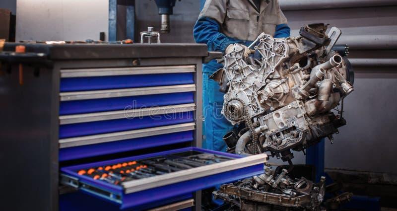 Réparation de révision Le jeune mécanicien automobile démantèle le moteur de opposition pour le diagnostic et la réparation au st photo stock