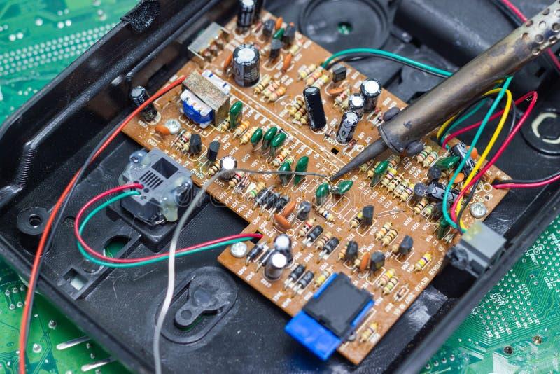 Réparation de technicien électronique de la carte d'ordinateur par les fers à souder photographie stock libre de droits