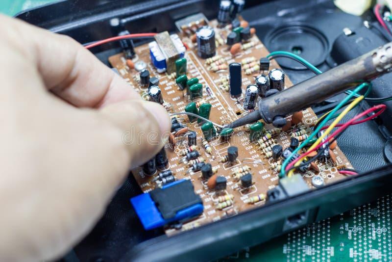 Réparation de technicien électronique de la carte du ` s d'ordinateur par les fers à souder photos stock