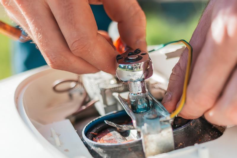 Réparation et entretien du chauffe-eau Le détail de fixation d'homme de la chaudière L'outil et les doigts se ferment  image stock