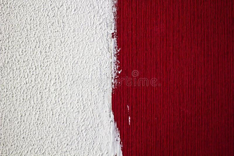 Réparations à la maison Le mur avec différentes textures, un demi- a peint blanc, l'autre rouge photo libre de droits