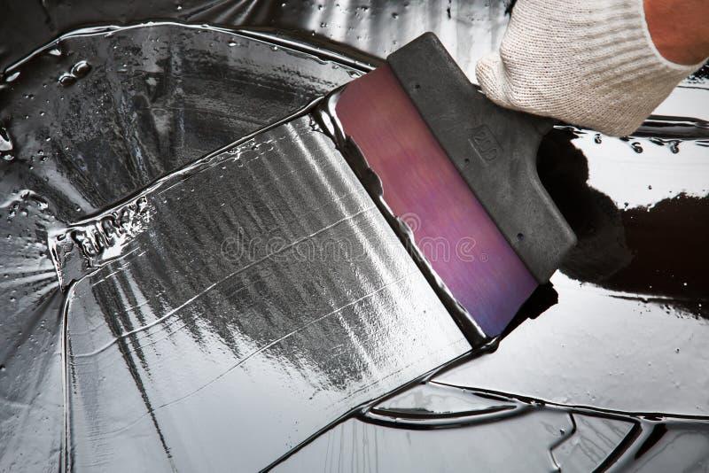 Réparations avec une spatule et un bitume images libres de droits