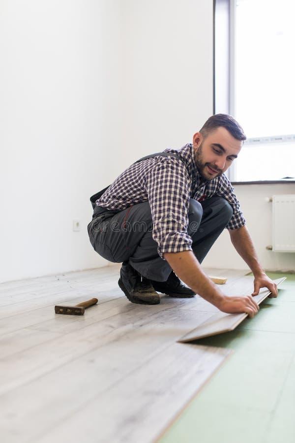 Réparez l'homme faisant l'installation en stratifié de plancher photo libre de droits