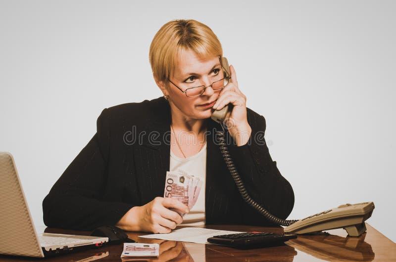 Réponse de attente de femme d'affaires mûre au téléphone avec l'argent photos libres de droits