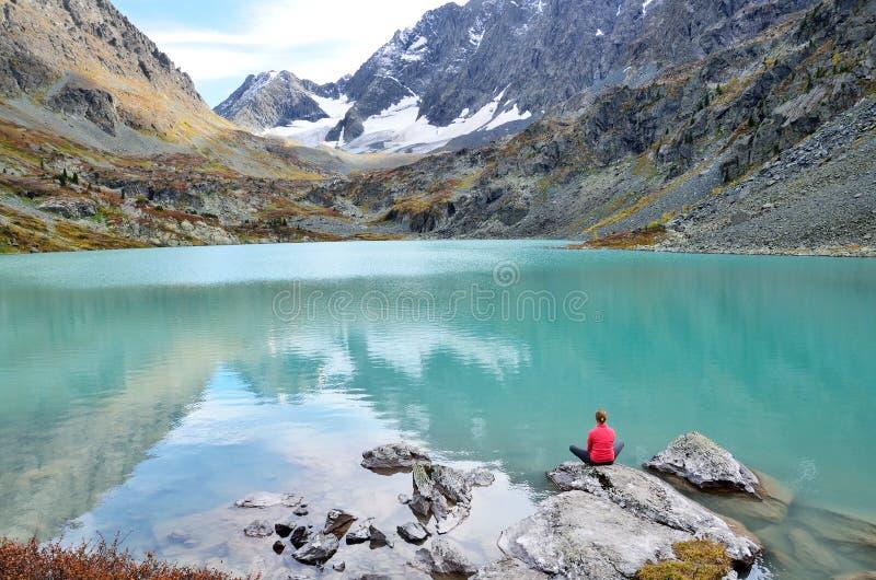 République d'Altai, secteur d'Ust-Koksinsky, Russie La jeune femme médite sur une pierre sur le lac Kuiguk Kuyguk photographie stock libre de droits