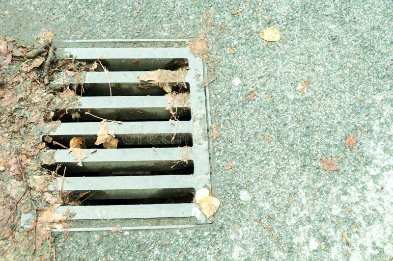 Réseau d'égouts de drainage de rue avec la couverture de grille en métal photos stock
