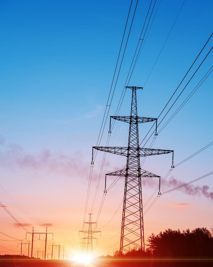 Réseau de distribution d'énergie - pylônes de l'électricité contre le coucher du soleil orange et jaune photo libre de droits