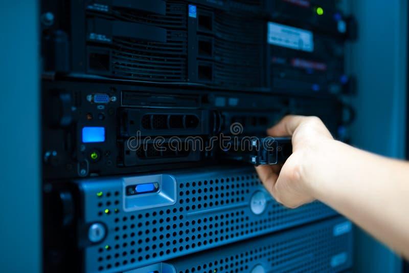 Réseau de serveur de difficulté d'homme dans la chambre de centre de traitement des données photo stock