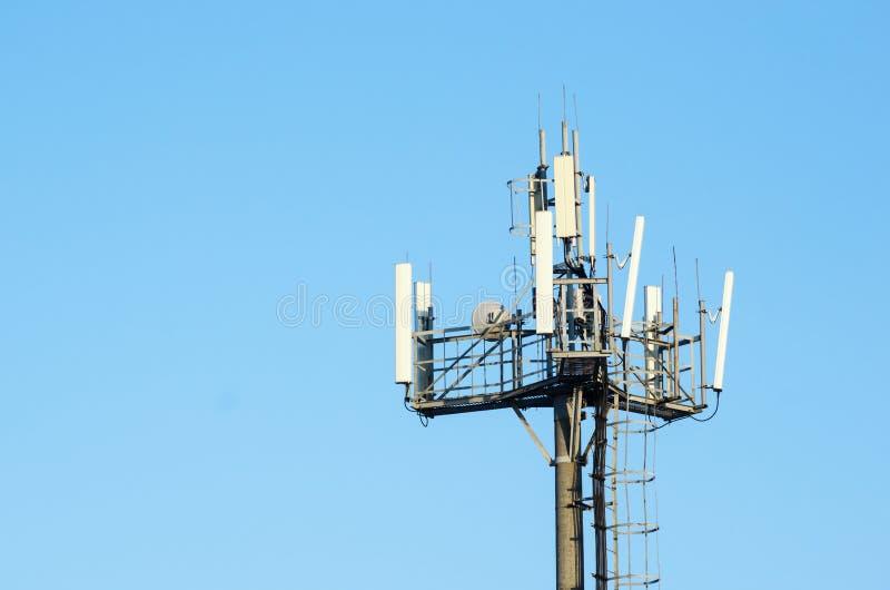 Réseaux cellulaires d'antenne contre le ciel clair bleu photos stock
