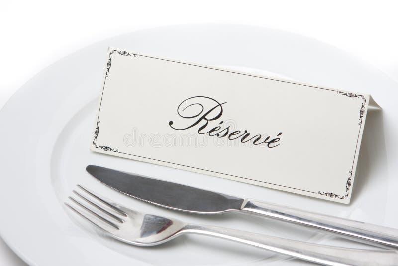 Réservé signez en français avec la fourchette et le couteau image stock
