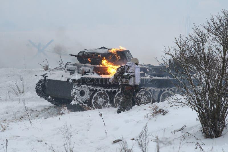 Réservoir allemand capitonné PzKpfw II Ausf D et soldats allemands en fuite Fragment de la reconstruction des batailles de la gra image stock