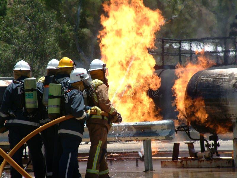 Réservoir de gaz sur le feu avec des pompiers de secours images stock