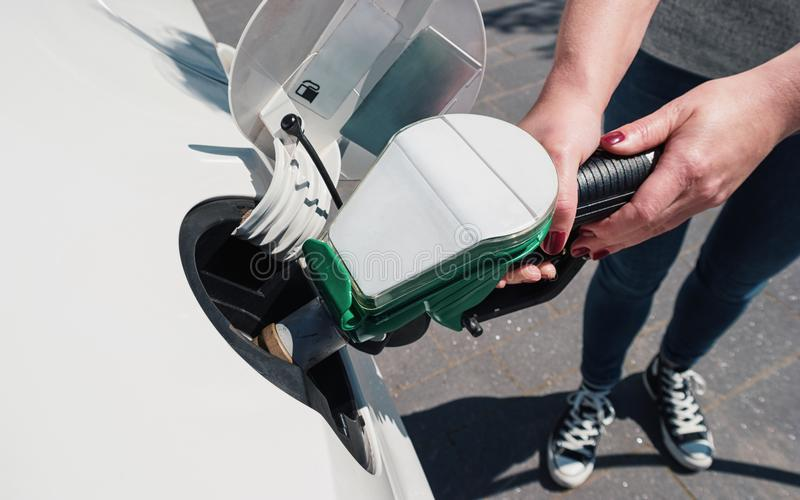 Réservoir de voiture de ravitaillement de jeune femme à une station de carburant images stock