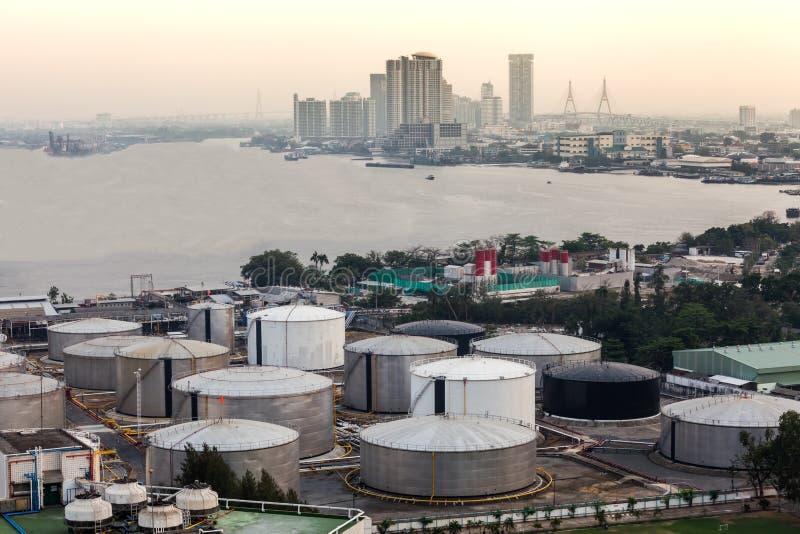 Réservoirs de stockage de pétrole industriels dans une raffinerie avec le paysage urbain de bâtiment photo stock