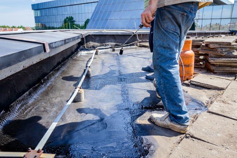 Résine d'installation de toiture avec le chalumeau de propane utilisant un Bu de gaz photo libre de droits