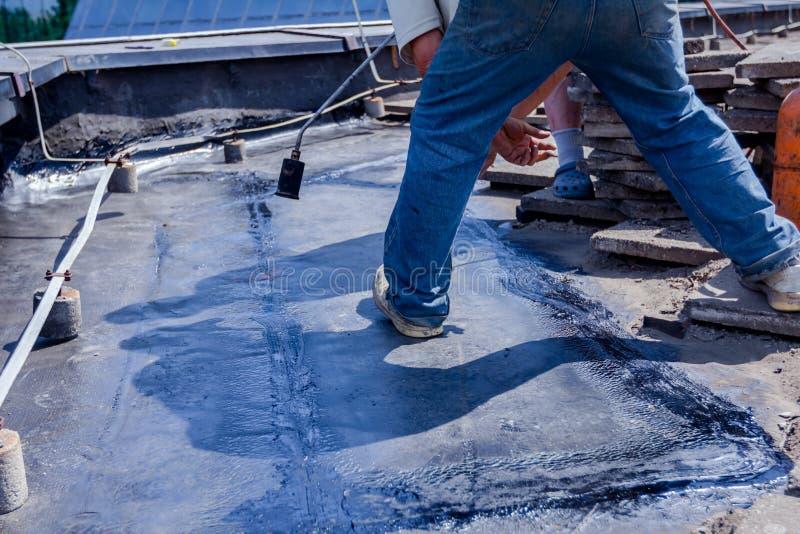 Résine d'installation de toiture avec le chalumeau de propane utilisant un Bu de gaz photo stock
