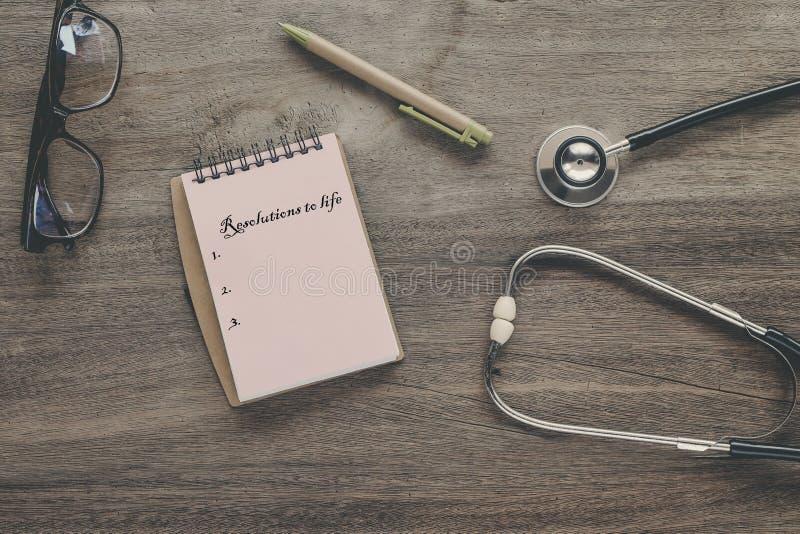 Résolutions au texte de la vie sur la note de livre avec le stéthoscope, image libre de droits
