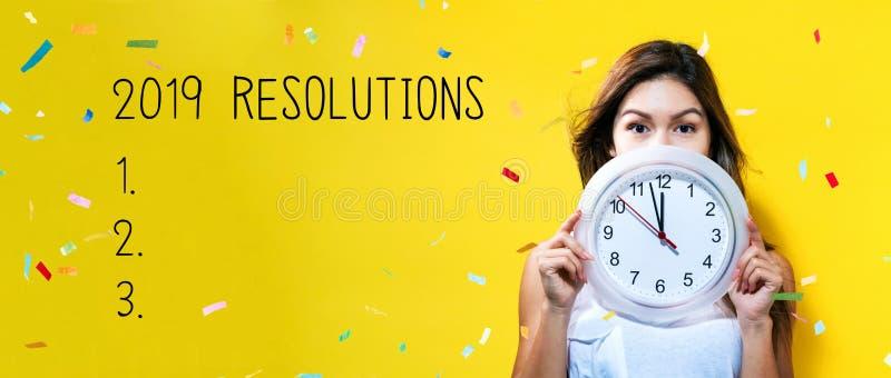2019 résolutions avec la jeune femme tenant une horloge photo stock