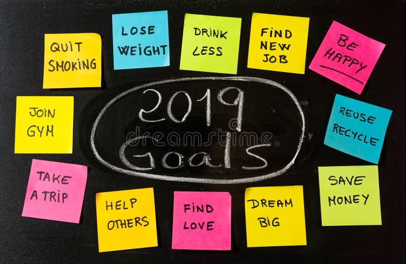2019 résolutions de buts ou de nouvelle année marquent l'écriture et les notes à la craie colorées de note de post-its sur le tab image stock