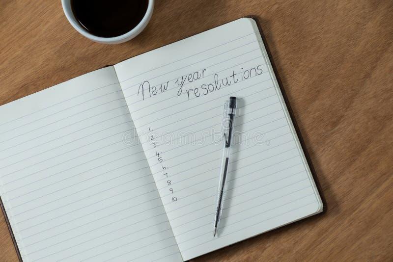Résolutions de nouvelle année écrites sur le journal intime avec la tasse de café photos libres de droits