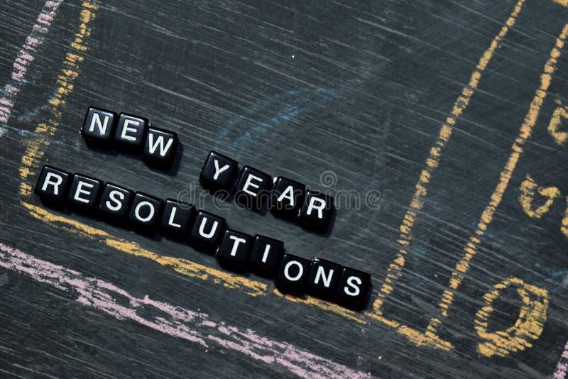 Résolutions de nouvelle année concernant les blocs en bois Image traitée croisée avec le fond de tableau noir images libres de droits