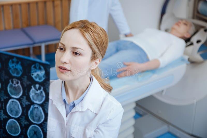 Résultats de examen d'oncologiste féminin sérieux du balayage de CT photo libre de droits