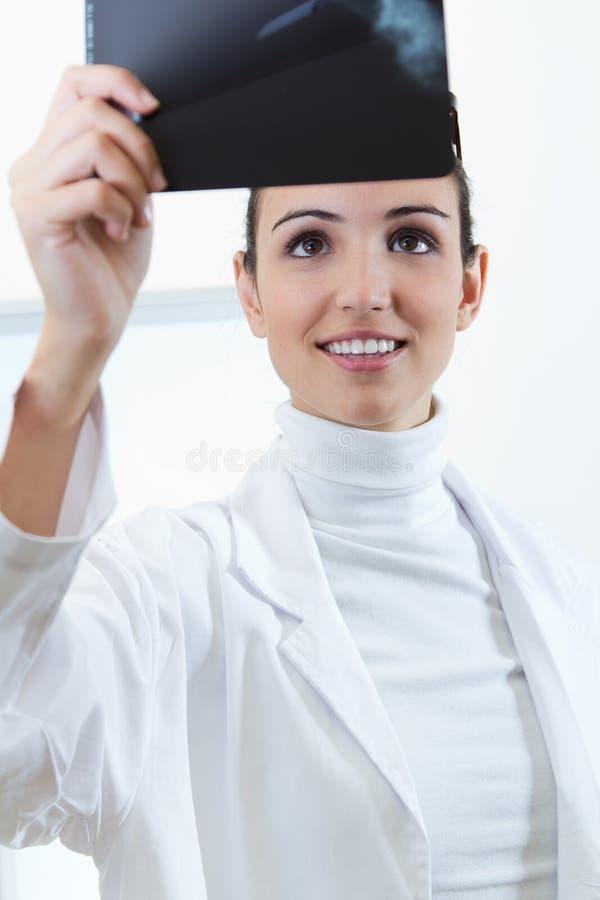 Résultats de examen de rayon X de jeune docteur féminin attirant image stock
