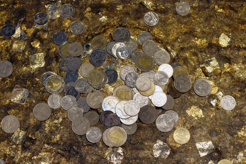 Résumé beaucoup de l'argent thaïlandais de pièce de monnaie faisant le mérite pour le foyer sélectif de fond, pièce de monnaie d' photos stock