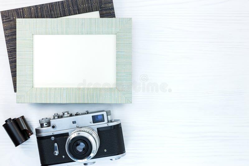 Rétro appareil-photo avec le petit pain de film et deux cadres vides de photo sur le blanc image libre de droits